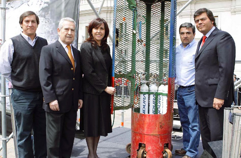 Indura personnel pose with the Fnix capsule and Luxfer oxygen cylinders used in the successful rescue of 33 miners. They are (from left to right) Alberto Perez, Engineering Projects Manager Ren Le Feuvre, Corporate Commercial Manager  Alicia Morales, Medical Business Development Manager Alejandro Symmes, Gases and Specialty Mixtures Manager and Cristin Barra, Consultant from the Chilean Government Ministry of the Interior.
