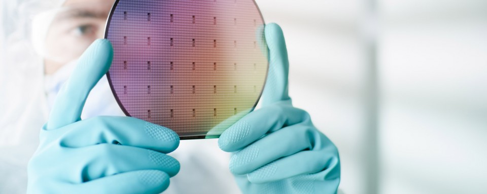 Scientist examining circular silicon wafer